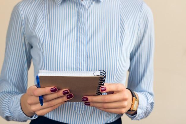青い縞模様のシャツのバーガンディのマニキュアを持つ女性はノートを保持します。