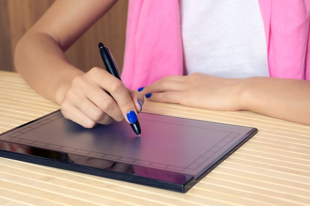 ピンクのスカーフと青いマニキュアの女性は、木製のテーブルのクローズアップでタブレットに描画します