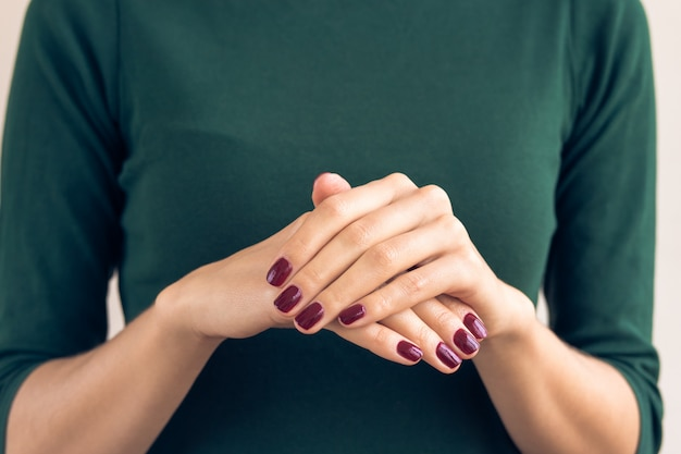 Женщина в зеленой футболке показывает руки с бордовым маникюром