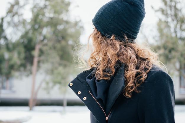 婦人服の詳細:黒いコートを着た巻き毛を持つ少女と公園内の屋外キャップクローズアップ
