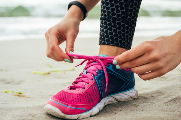 マニキュアネクタイと女性の手をビーチでピンクとブルーのスニーカーにひもで締めます