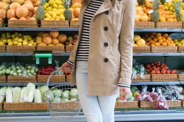 Девушка в супермаркете выбирает овощи и фрукты