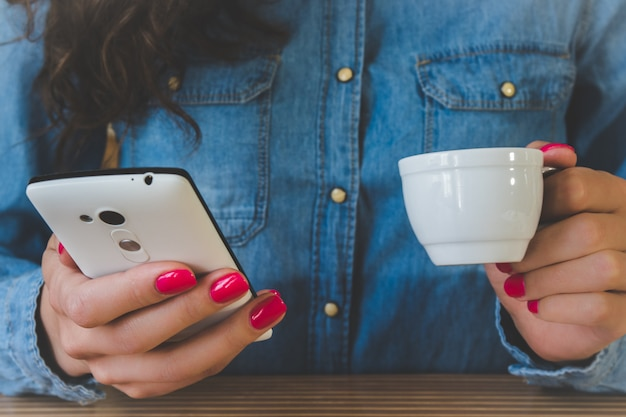 コーヒーを飲みながら電話を楽しんでいるデニムシャツの女の子