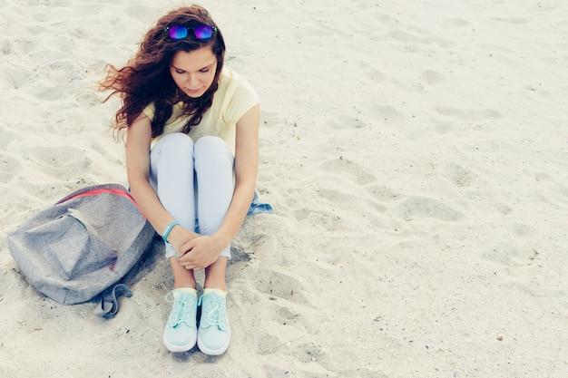 Красивая молодая брюнетка в солнцезащитных очках, футболке и джинсах сидит на пляже