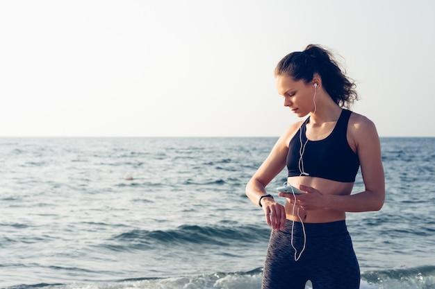 Девушка на пляже держит мобильный телефон с наушниками в руке и проверяет данные с помощью умных часов