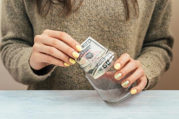 Девушка в коричневом свитере с желтым маникюром кладет деньги в стеклянную банку, крупный план