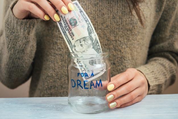 Женщина в коричневом свитере с желтым маникюром кладет деньги в стеклянную банку, крупный план