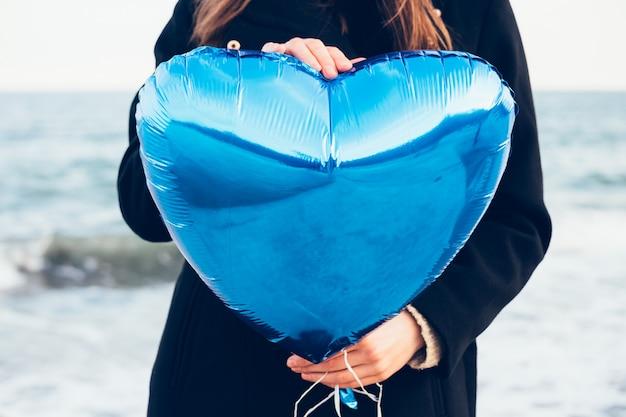 海の背景にハートの形の青い風船を持って黒いコートの女の子