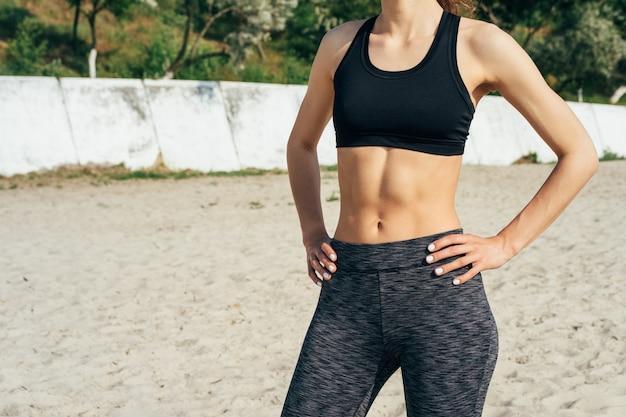 Спортивная девушка в штанах и топ стоя на песке и держась за руки на бедрах