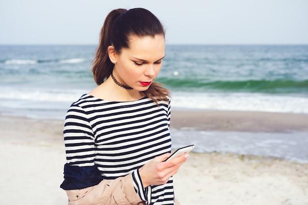 手にスマートフォンでビーチを歩いて魅力的な若い女性