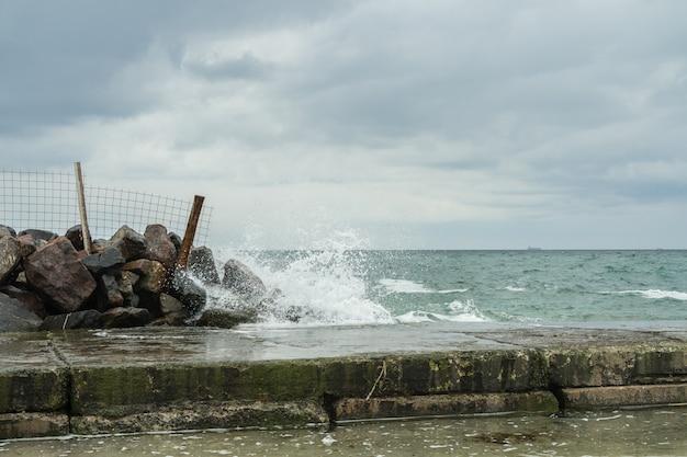 Волны разбиваются о скалы возле пирса