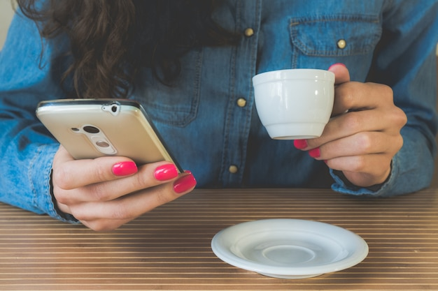 若い女の子はコーヒーを飲み、カフェで携帯電話を楽しんでいます