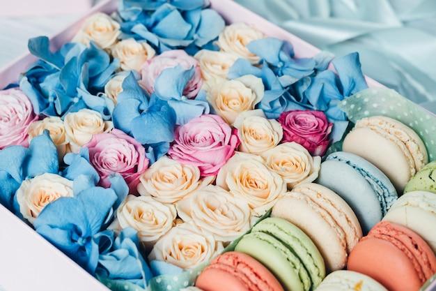 カラフルなバラとマカロニ、テーブルの上のピンクのボックス