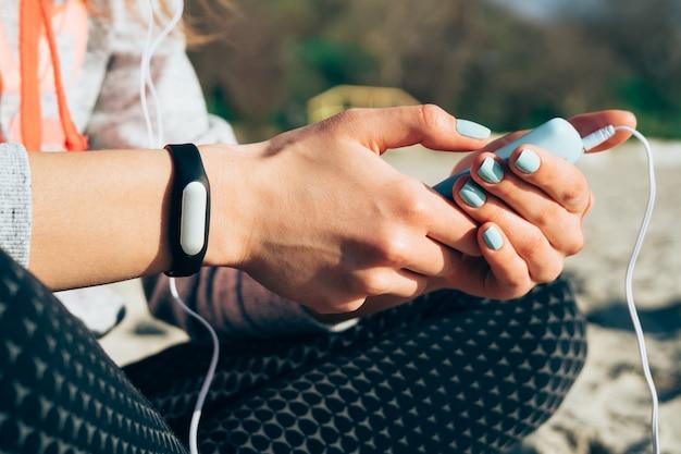 ビーチに座っていると、スマートフォンのヘッドフォンで音楽を聴いている女の子のクローズアップ