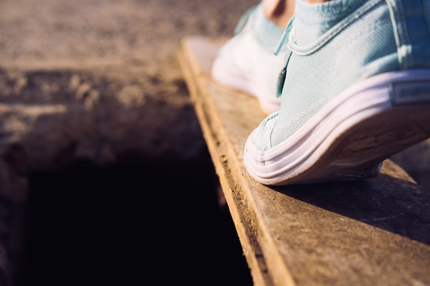 大きなピットの上の狭い板の上を歩くスニーカーの女性の足