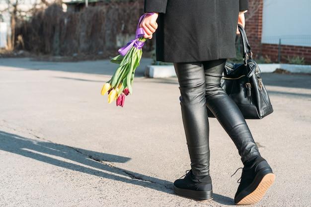 花の明るい花束と通りを歩いて黒い服を着た女性