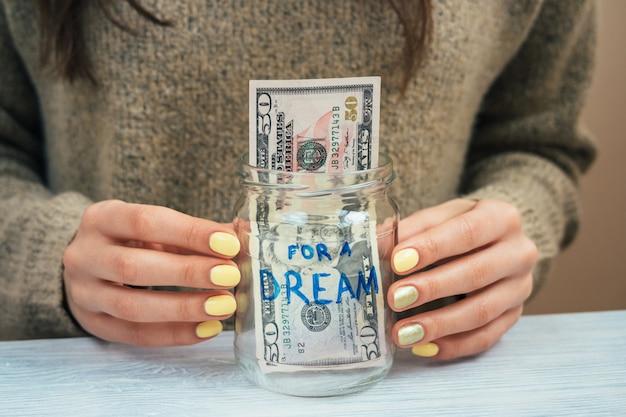 Девушка в коричневом свитере с желтым маникюром держит стеклянную банку с деньгами, крупный план