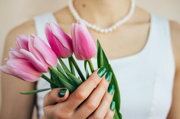 Красивая женщина в белом платье и жемчужное ожерелье держит розовые тюльпаны