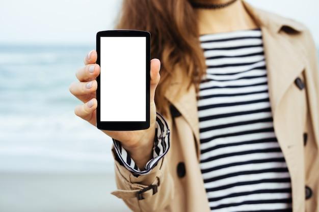 Девушка в бежевом пальто и полосатой футболке показывает пустой экран телефона на фоне моря
