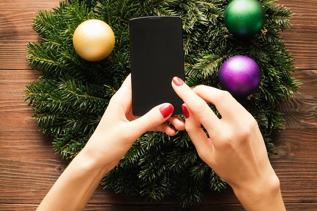 クリスマスの装飾の背景にタッチスクリーンで携帯電話を保持している赤いマニキュアと女性の手