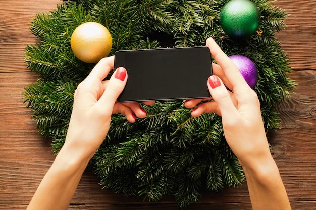 クリスマスの装飾の背景にタッチスクリーン付きの携帯電話を保持している赤いマニキュアと女性の手