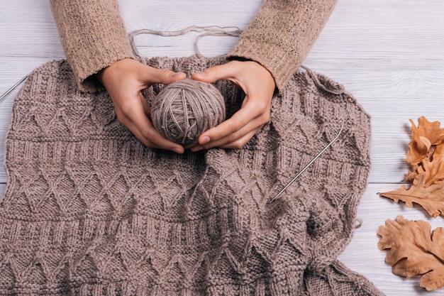 背景ニットセーターでウール糸のボールを保持している女性の手の上から見る