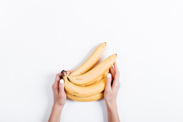 Женская рука держит гроздь бананов на белом столе