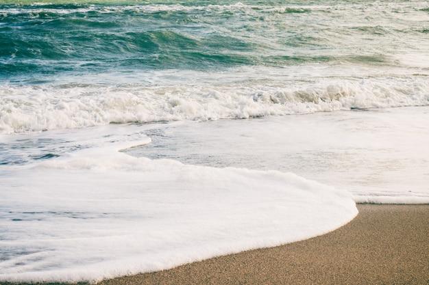海の波とレトロな色の浜辺の砂