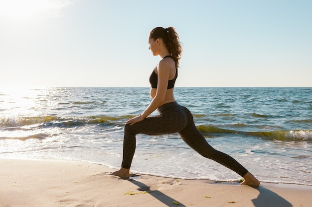 Спортивная девушка на пляже делает упражнения выпады