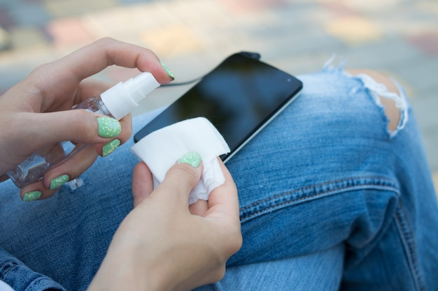 携帯電話を掃除するためのスプレーと布を持っている女性の手