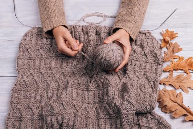 編み物とテーブルの上のウール糸のボールを保持している女性の手の上から見る