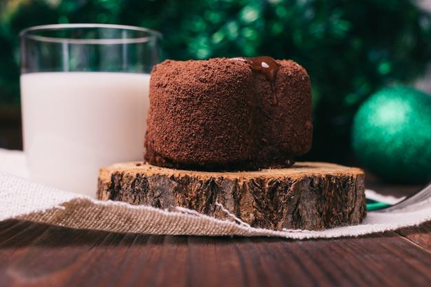 チョコレートケーキ、牛乳と木製のテーブルの上のクリスマスの装飾のガラス
