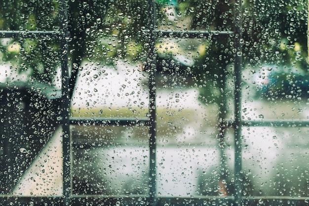 夏の雨の間に滴で濡れている窓