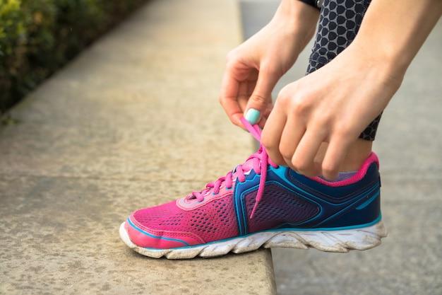 マニキュアネクタイと女性の手は公園でジョギングしながらピンクとブルーのスニーカーにひもで締めます