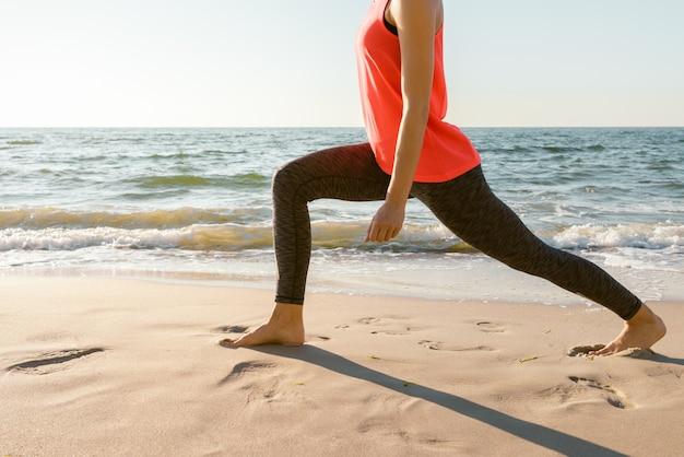 Стройная спортивная женщина в красной рубашке занимается растяжкой босиком на пляже в лучах утреннего солнца