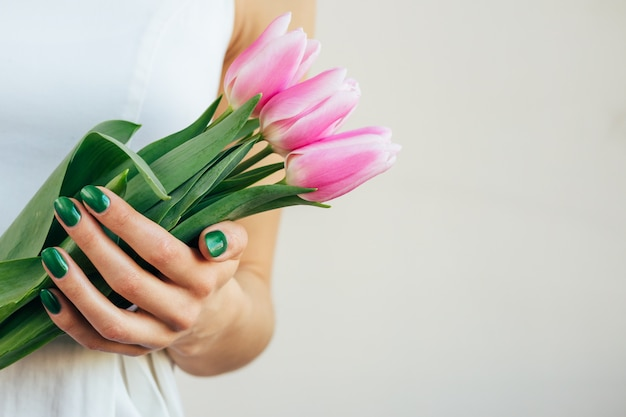 Женские руки с зеленым маникюром, держа розовые тюльпаны на бежевом фоне