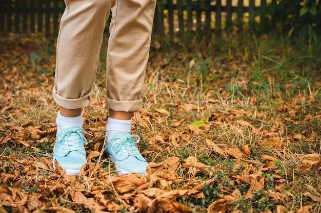 落ち葉にはベージュ色のズボンとターコイズ色のスニーカーの女性の足があります