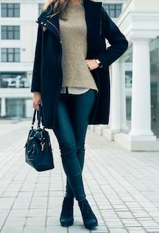 Женщина в свитере, черном пальто и штанах держит сумки во время прогулки по городу