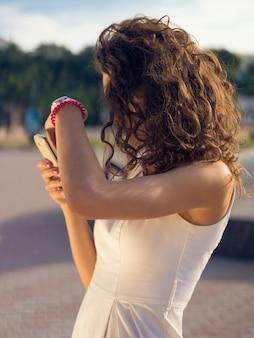 若い女の子は明るい日光の下で彼女のスマートフォンの画面上の情報を見ようとします