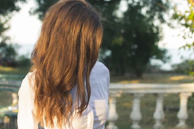 公園を歩いて細い赤髪の女夏の晴れた日