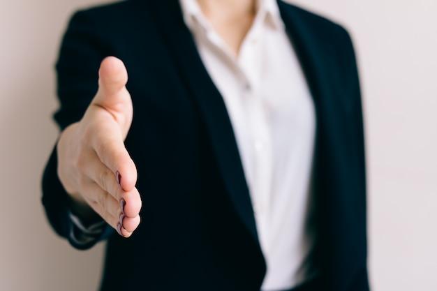 ビジネススーツの女は、握手のクローズアップのための彼女の手を差し伸べる