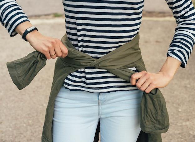 Женщина в полосатой футболке завязывает рукава зеленого пиджака на талии