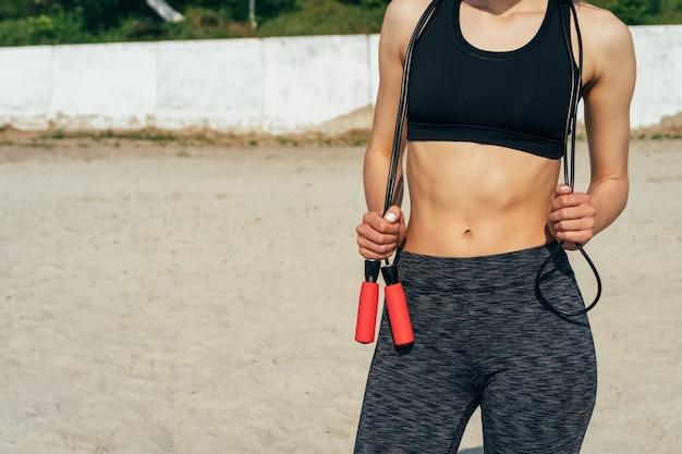 朝のビーチで彼女の手で縄跳びの縄でスポーツウェアの女