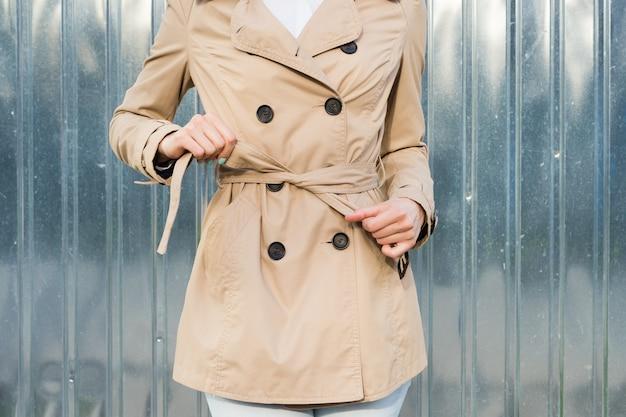Крупный план женщины связывает пояс на пальто на открытом воздухе