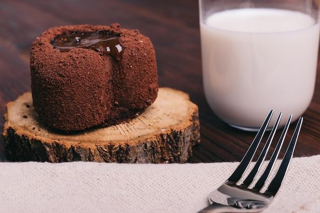 チョコレートケーキと茶色のテーブルの上のミルクのガラス、テーブルクロスの上のフォーク