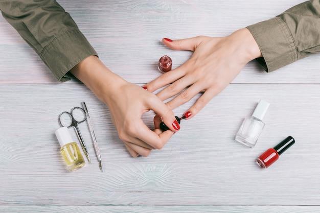 Женщина делает маникюр и красит ногти в красный