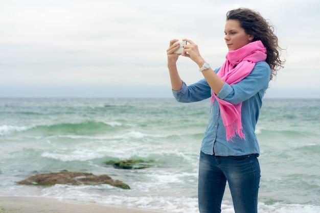 巻き毛を持つ若い女性は海辺の絵になります
