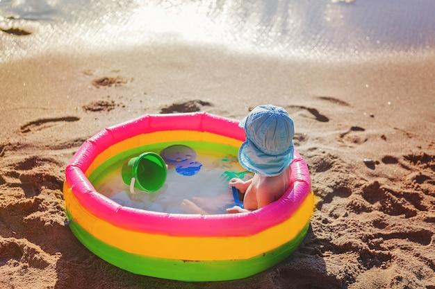 小さな子供用プールの海のそばに座っているキャップで子供