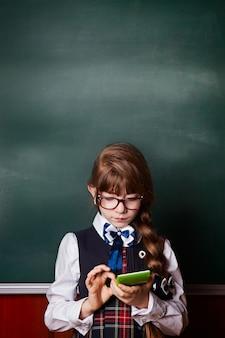 Девушка в школьной форме, глядя на калькулятор и подсчета