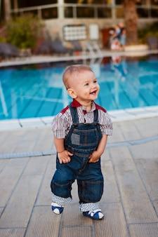 ジーンズの子供がジャンプスーツを着て、笑って目をそらして、最初のステップ